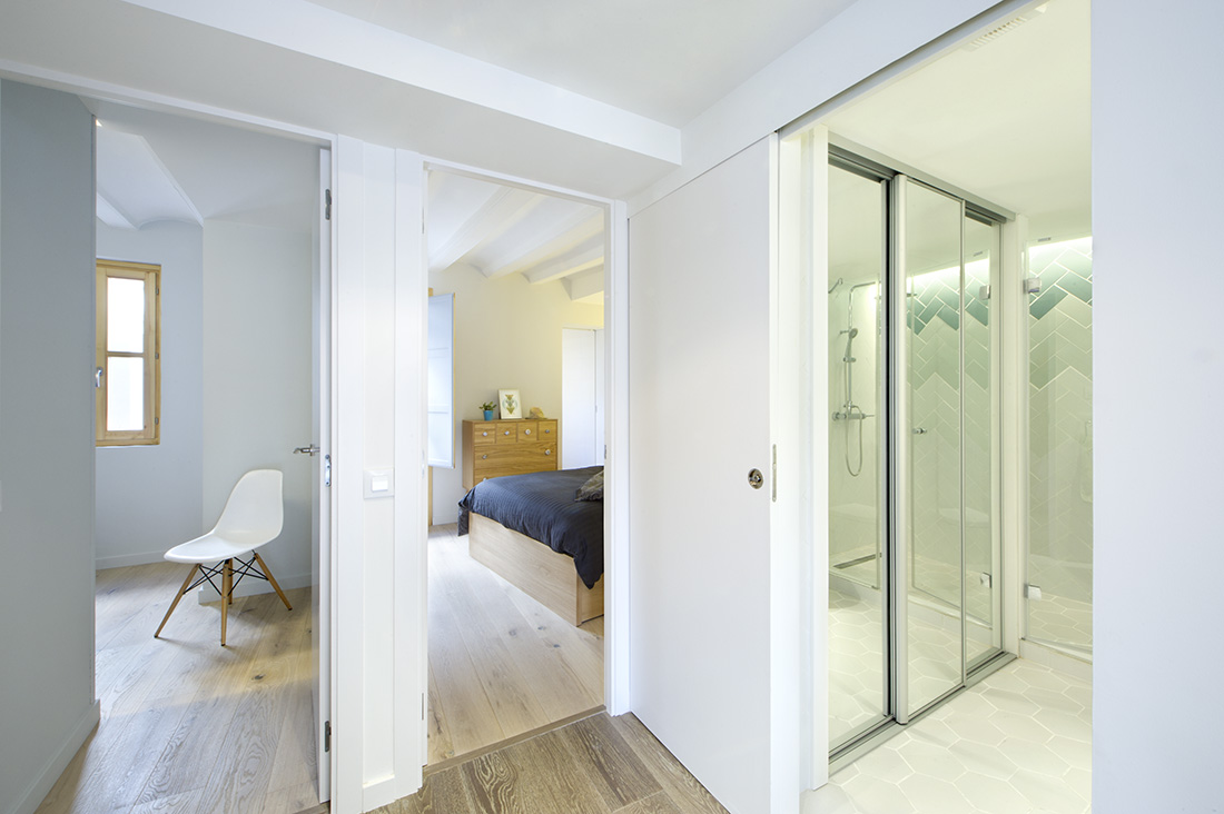 The bedrooms are located with an accessible bathroom. The painted ceiling still exposes the bare figure of the beams.