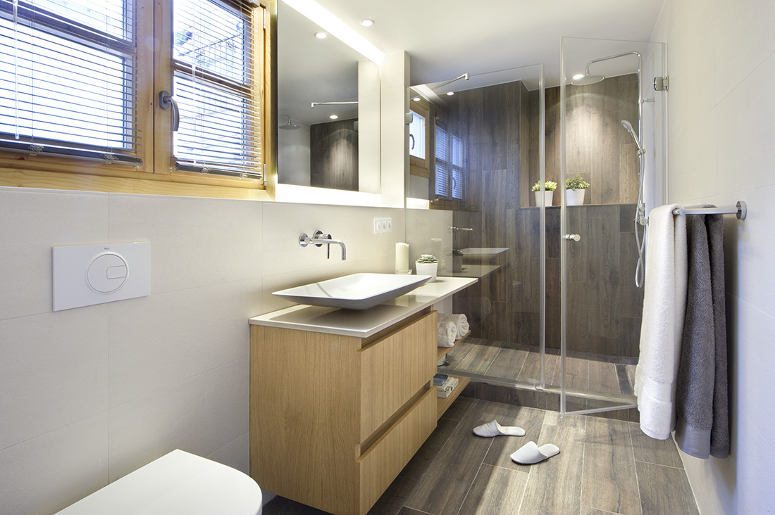 An earth toned bathroom is located right inside the bedroom. It has a nice wood plank flooring, a sink, toilet bowl and a shower area with glass door.