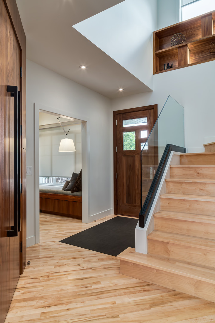 A glass railing on the staircase provides a bright and expansive feeling to the front entryway.
