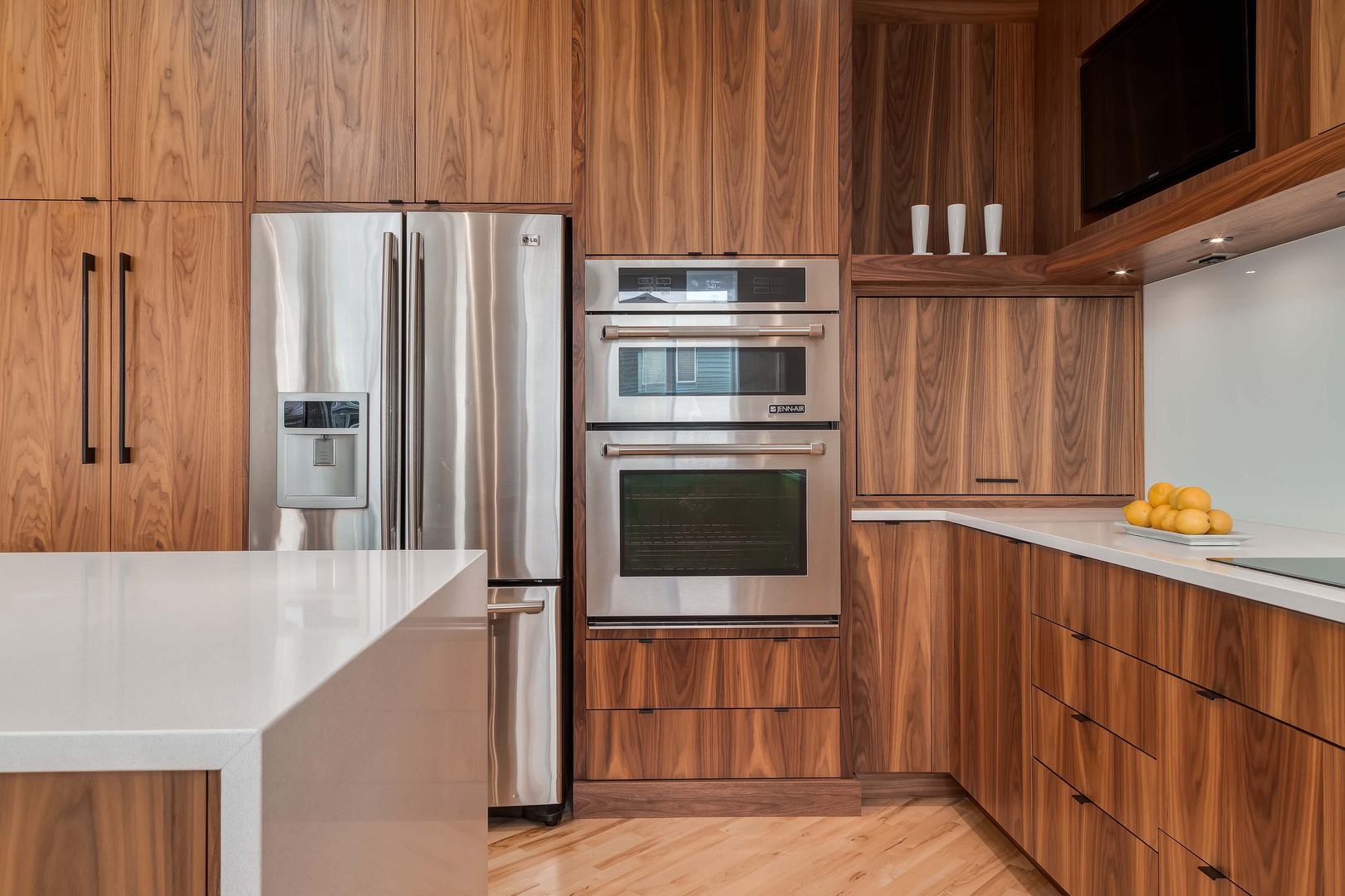 The stainless steel appliances here enhance the natural wood grain pattern.