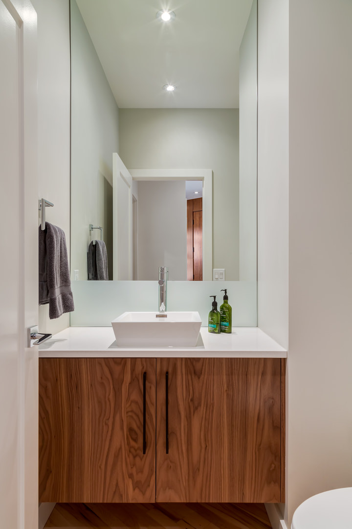 A compact half-bath with beautiful walnut cabinet and a contemporary sink.