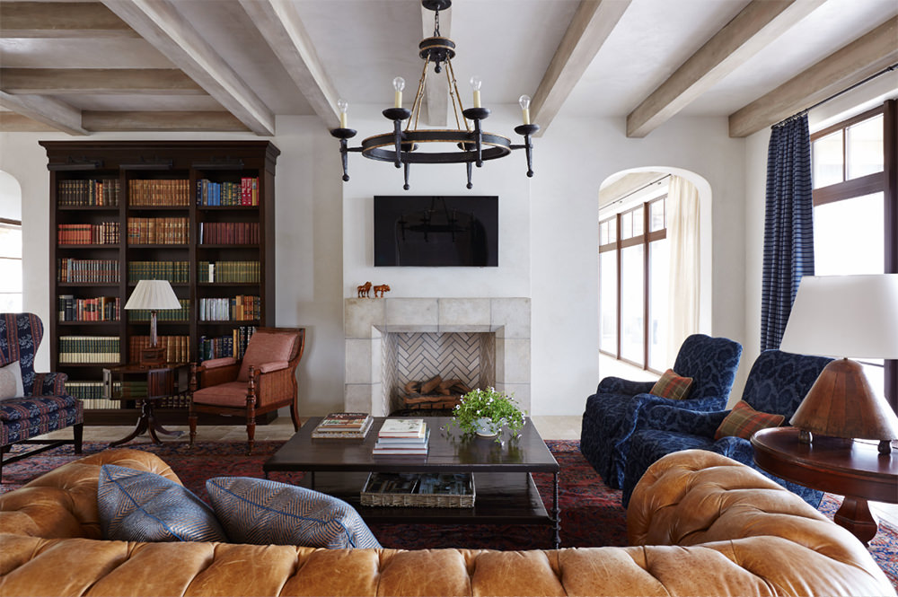 The beauty of the symmetrically balanced and exposed beams on the ceiling strike a simple and plain linear effect on this hyped up living space populated with overstuffed sofa and chairs in blue and ochre tone covers. No other accessories are added except a few books, flower vase, figurines and lampshades, which are common in any designs. Wide open windows and natural lighting have been the facet of contemporary designs.