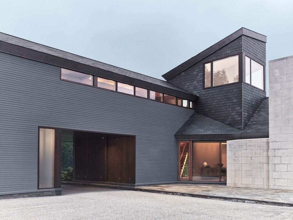 the house presents itself as three wings with juxtaposed pitched and shed roofs