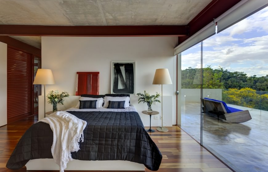 Notice how the large window makes the bedroom look so much larger. This bedroom was designed by Denise Macedo Architects.