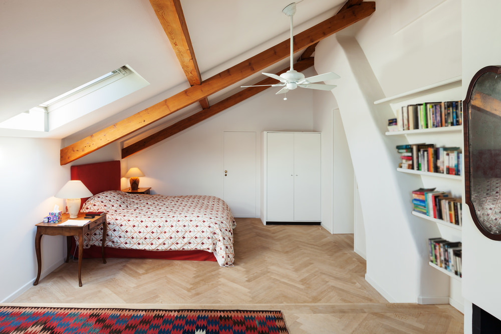 When you have a sloped ceiling in your bedroom, it's a good idea to place the head of the bed under the lowest part of the ceiling.