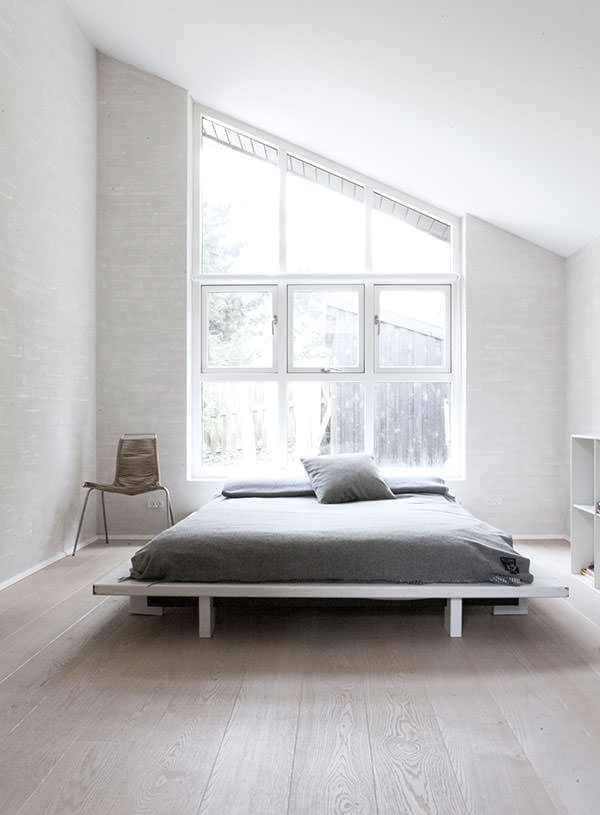 The above bedroom is a small space but appears larger with the vaulted ceiling, light color scheme, low bed and minimalist decor.