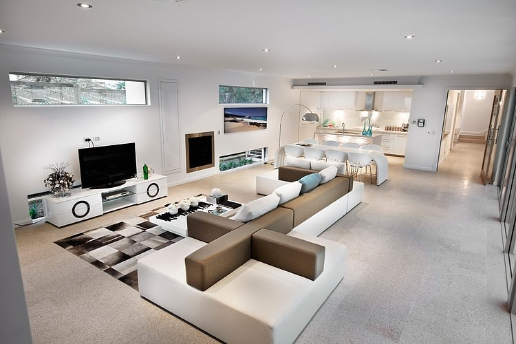 Another open concept, this one showcasing geometrical artistry. The off-white sofa with a brown back and arm rest is fashionable and sleek. There are square patterns on a floor rug and circles on the TV stand. A few matching frames, pillows and decors complete the picture.