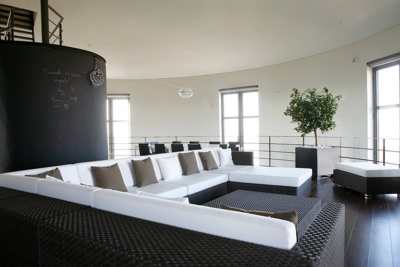A sleek contemporary design living room with only two major tones, dark brown and white. The only other colors come from the slightly lighter brown pillows and the potted greenery.