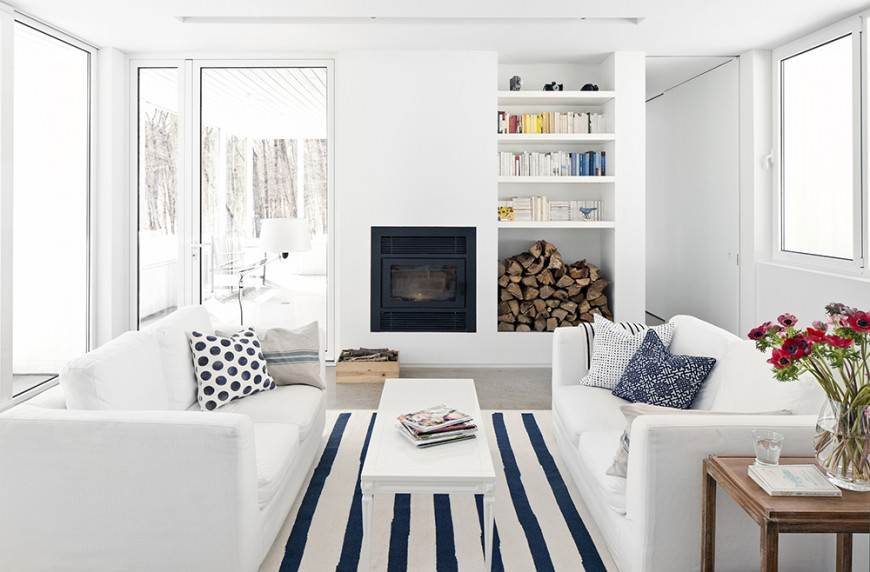 Nicely arranged living room with white furniture accented with blue from the striped floor rug and patterned throw pillows. The firewood piled on the white shelf and the wood corner table decorated with some blossoms give a little diversion from the pure white scenery.
