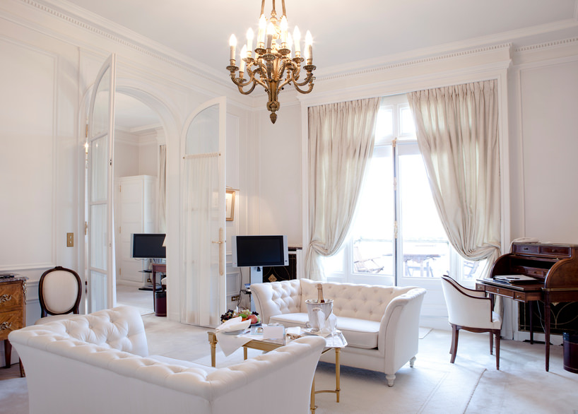 This is a fairly traditional living room touched up with white from the floor to the ceiling. The curtains are white, the floor rug is white, and the sofa set is white. There's some contrast, however, with the dark color of the woods coming from the cabinets and piano set.