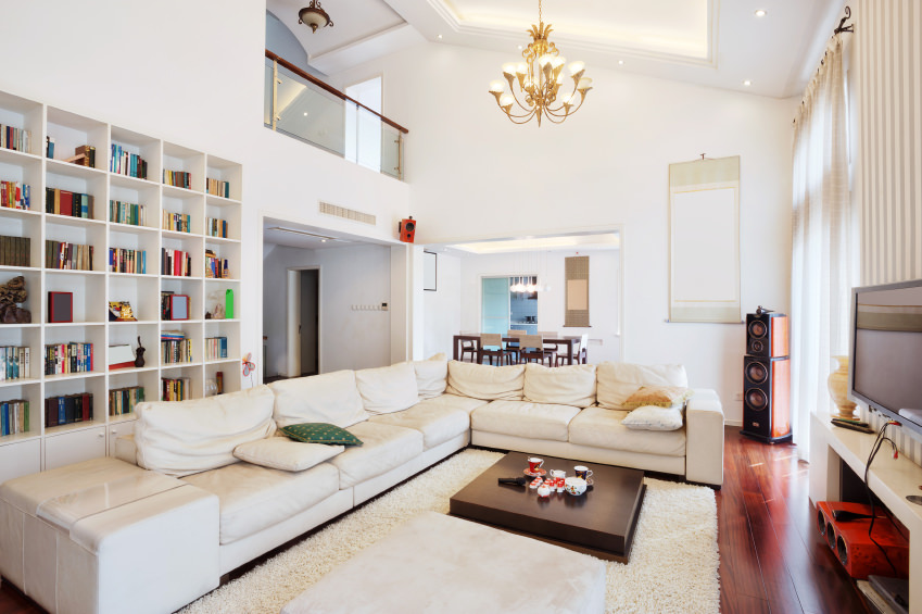 This white library living room is stretched by a long off-white sofa angled on the wooden floor. The matching floor rug and pillows add to the brightness, and in the center sits a low wooden tea table for contrast.
