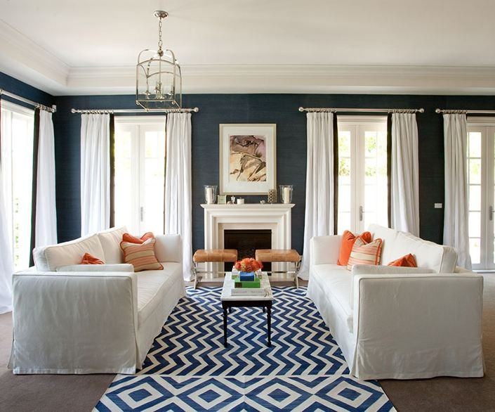 The shades of blue on the wall and the patterned floor rug match nicely with the white ceiling, curtains and sofa set.
