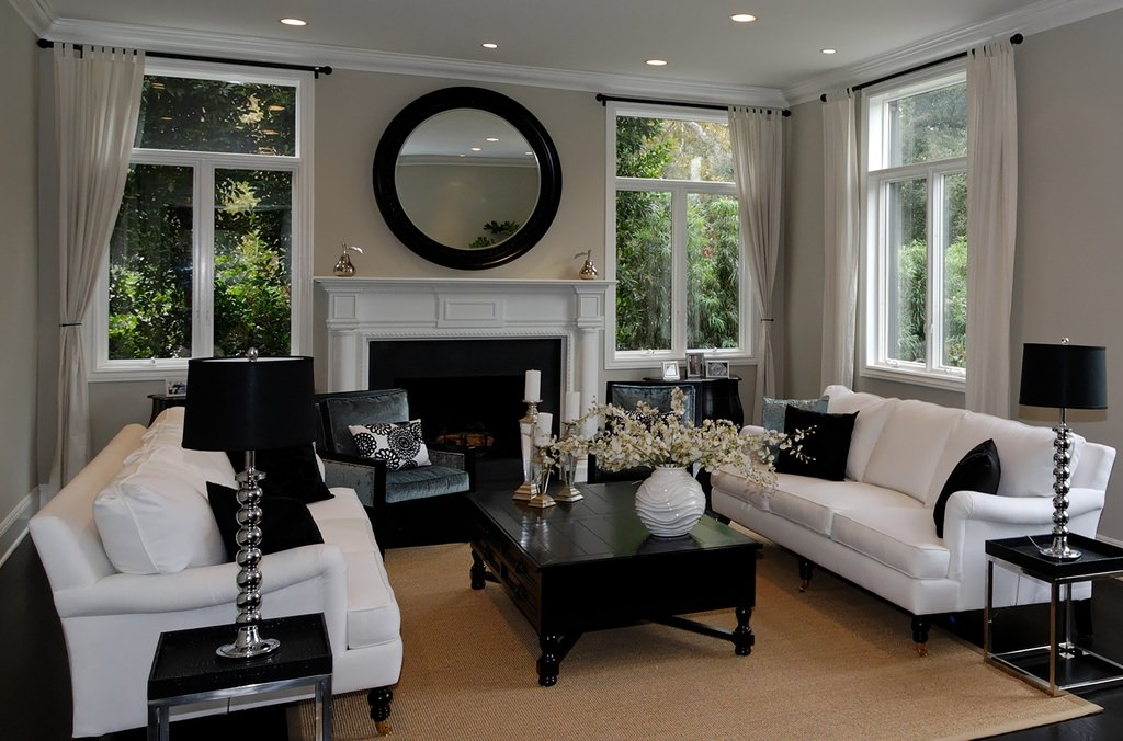 An elegant living room dominated by black and white where the white sofa set is paired with black throw pillows and the black wooden center table. Lampshades mounted on a black corner table top are also black, but their metallic stands add a bright and offbeat detail.