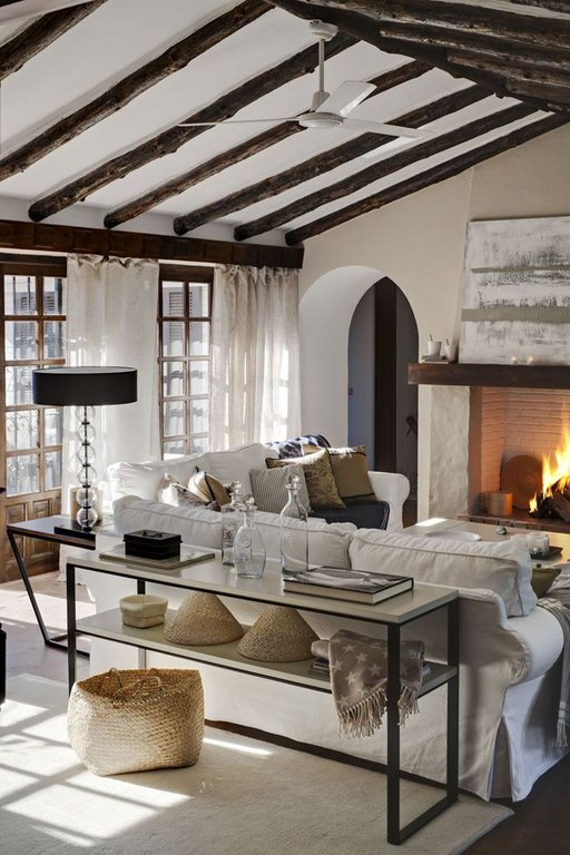 The rugged native look of the living room is made even more attractive by the exposed log beams on the white ceiling.