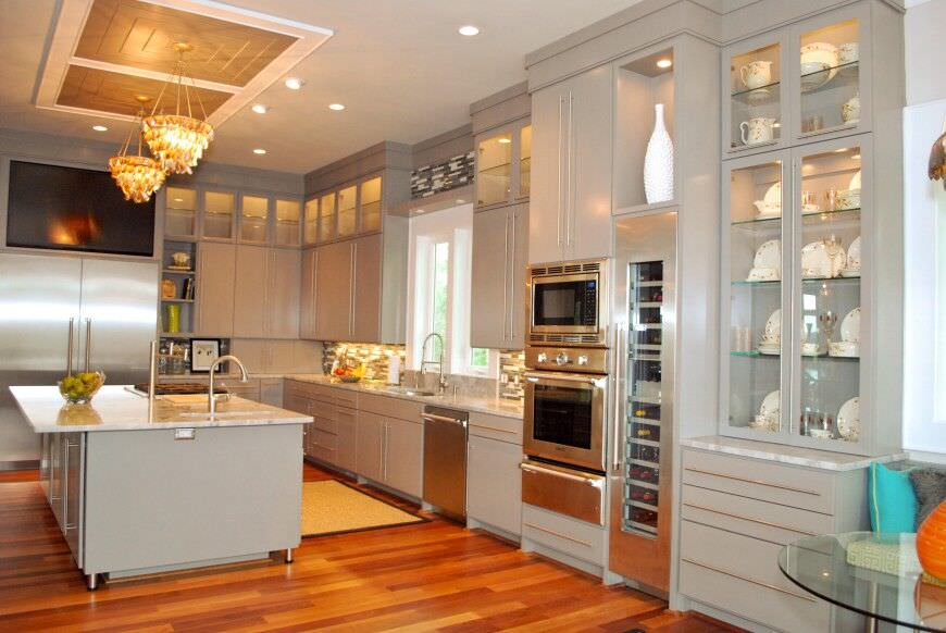 Off-white kitchen design with a double stainless steel oven adjacent to a full wine fridge.