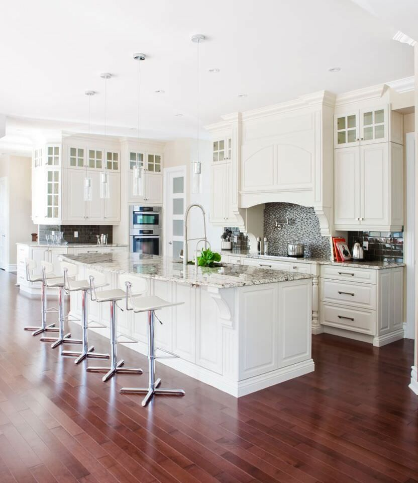 Gorgeous white kitchen with double stainless steel wall ovens tucked in the corner of the kitchen.