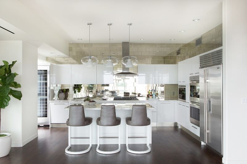White kitchen with dark wood floor with a double wall oven placed next to the stainless steel refrigerator.