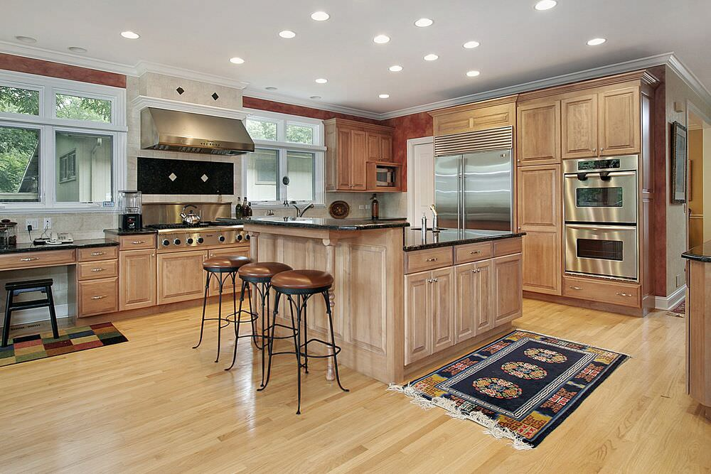 Massive light wood kitchen with lighter wood floors featuring a massive chef's stove and double wall oven.