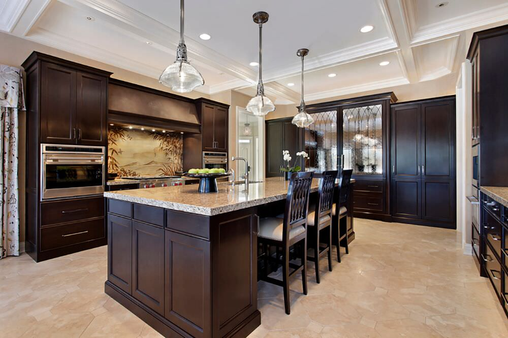 Luxurious kitchen design with rich wood throughout, loads of storage, a large island and two wall-mounted ovens.