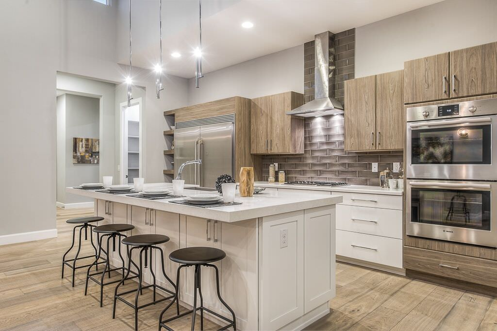 Contemporary kitchen with plank wood style floor, white and natural wood cabinets and a large double wall oven.