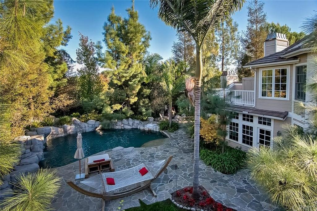 An oasis of a backyard surrounded by tall evergreens towering over a small, natural-looking kidney shaped pool. The gray flagstone patio is a perfect fit for this natural oasis backyard