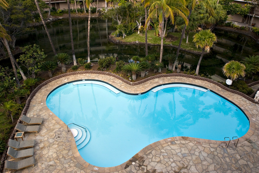 Another aerial view of a kidney style swimming pool. This one is surrounded by terraced gardens and palm trees which looks awesome.