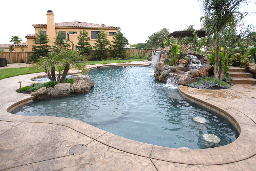 I love pools like this with rock waterfalls and trees. It really dresses up the backyard and make for both a fun and beautiful pool setting.