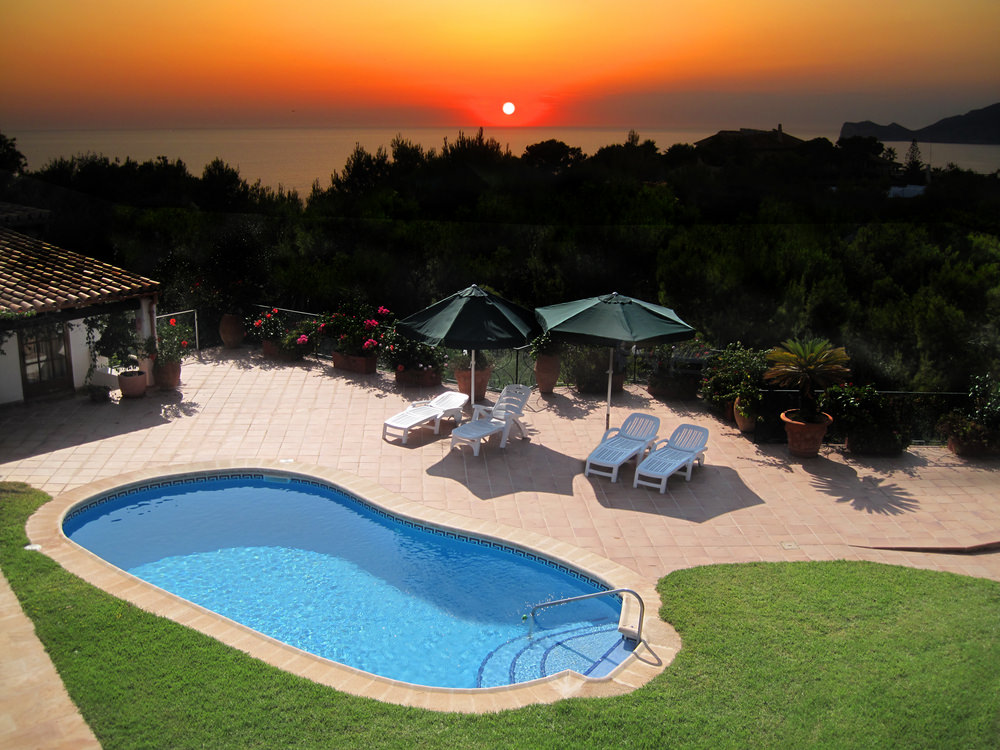Small kidney shaped pool overlooking the ocean at sunset