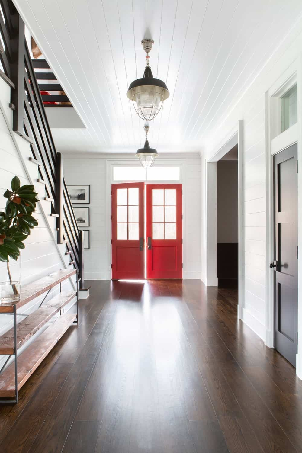 This is a beautiful and simple welcoming foyer with a pair of red wooden main doors that have glass panels on them bringing in an abundance of natural lighting to the dark hardwood flooring and white shiplap ceiling bearing pendant lights.