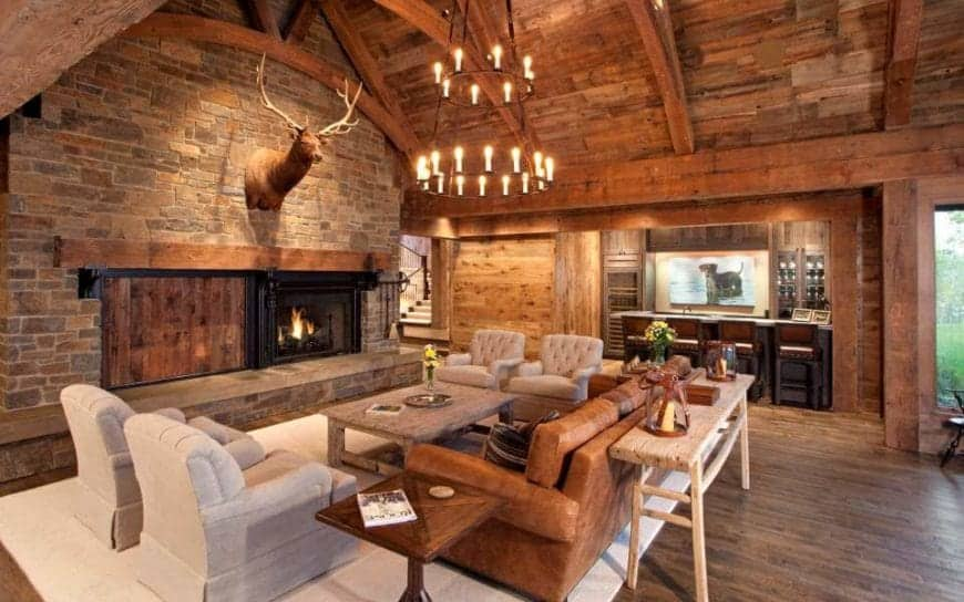 This comfortable living room has a wooden cathedral ceiling with exposed wooden beams. The majestic two-tier chandelier hangs over the wooden coffee table and brown leather couch that faces a stone wall adorned with a large fireplace and a large stuffed deer head.
