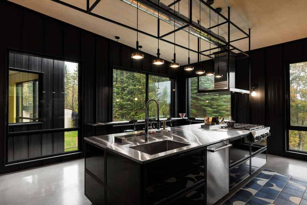 Even though this kitchen has black metal walls, it still managed to be bright and airy thanks to its large glass windows that feature the beautiful green landscape outside for that relaxing cooking experience on the black kitchen island that has a stainless steel countertop.