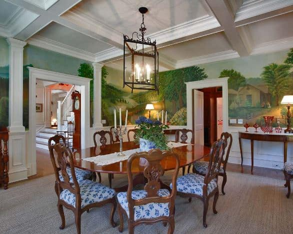 This elegant dining room has a white coffered ceiling that has a lantern-like pendant light over the oval dark wooden dining table and its wooden chairs contrasted by their white and blue seat cushions. This setup is given a nice background of walls dominated by a riverside farm mural.