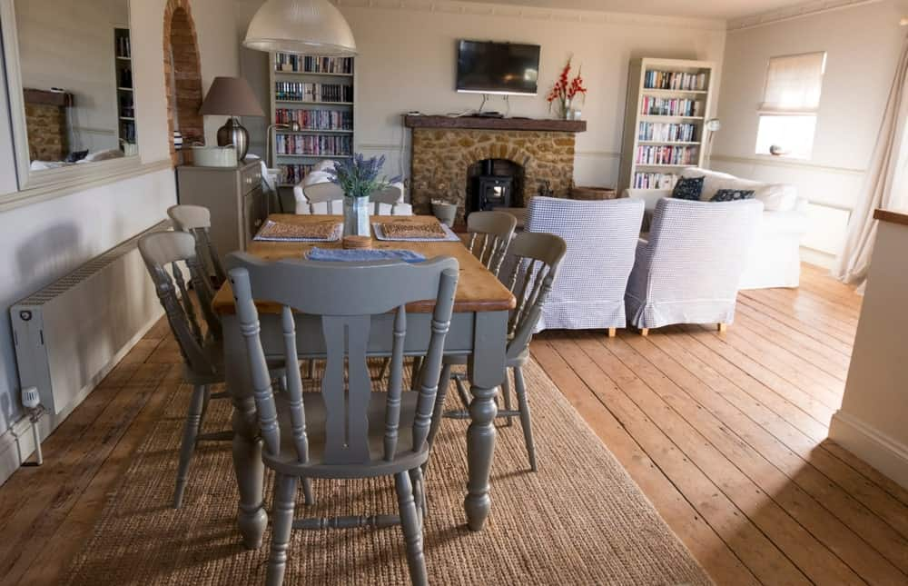This dining set has beautiful light gray wooden chairs with a classic design matching the legs of the rectangular wooden dining table. This is placed on a woven area rug over the hardwood flooring by the living room that has a fireplace.