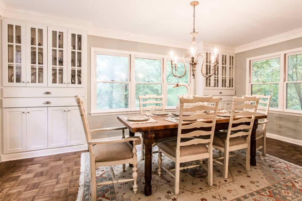 The lush green trees outside the glass windows adds a bit of color to the background of the wooden dining table that has contrasting white wooden chairs. These match with the light hue of the patterned area rug that is illuminated by the charming chandelier.
