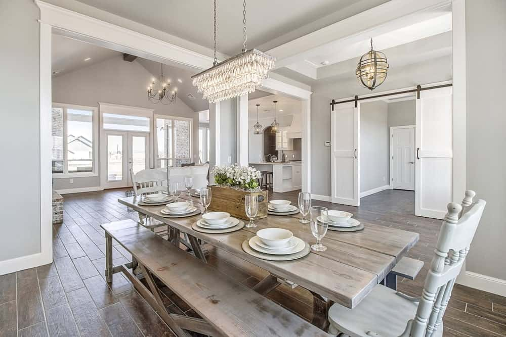 The rustic wooden dining table of this Country-style dining room is paired with a couple of wooden benches and white wooden chairs on each end. These stand out against the dark hardwood flooring but matches the light gray walls and ceiling.