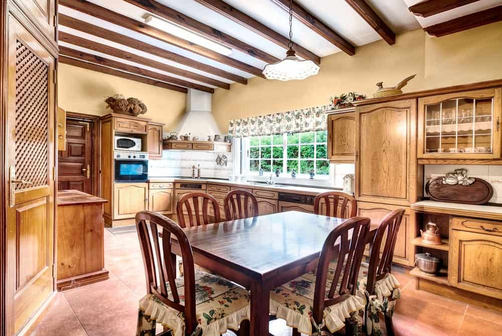 This is an informal dining area inside the kitchen that has terracotta flooring tiles. This complements the dark wooden table and its chairs of the same hue that is accented with floral seat cushions that matches the pendant light hanging from the exposed wooden beams of the ceiling.