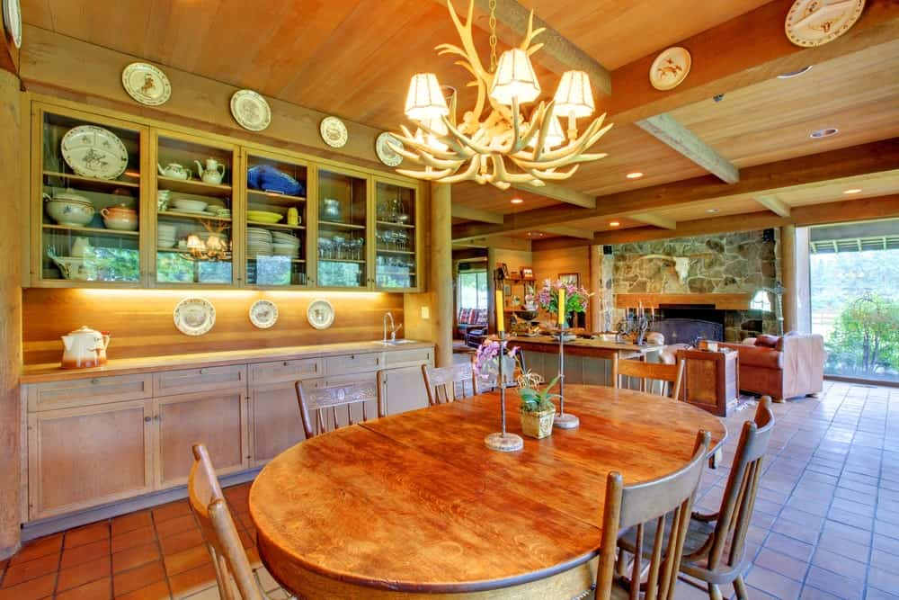 The highlight of this dining area inside the kitchen is the chandelier hanging over the elliptical wooden table. This chandelier is made of deer antlers casting off warm yellow lights onto the wooden ceiling adorned with decorative plates.