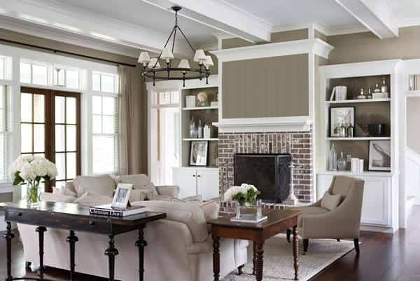 The white ceiling has exposed wooden beams with the same hue as the ceiling and the two built-in shelves that are flanking the fireplace surrounded with bricks. Across from this wall is the beige sofa set that looks comfortable and cozy.