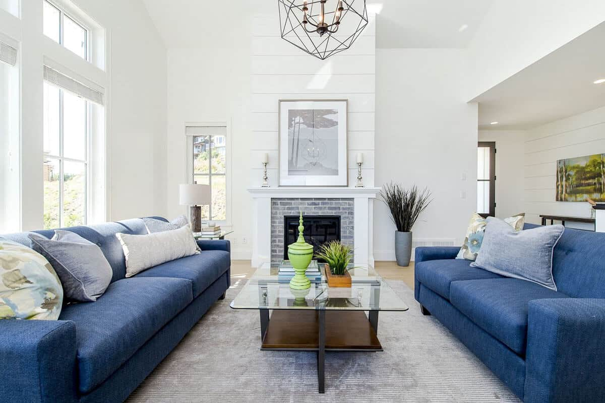 There are two beautiful blue sofas flanking a glass-top coffee table that stands in the middle of the light gray area rug facing a brilliant white wall with an elegant finish that houses the fireplace inlaid with gray bricks and a white mantle topped with a painting.