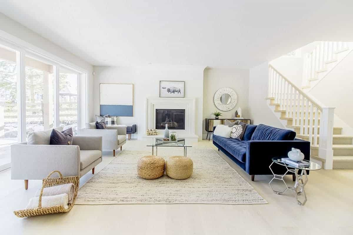 The brilliant white ceiling and walls are brightened by the large glass wall behind the two light gray cushioned armchairs facing a glass-top coffee table and a stand-out blue velvet sofa that contrasts the white brightness of the Farmhouse-style living room.