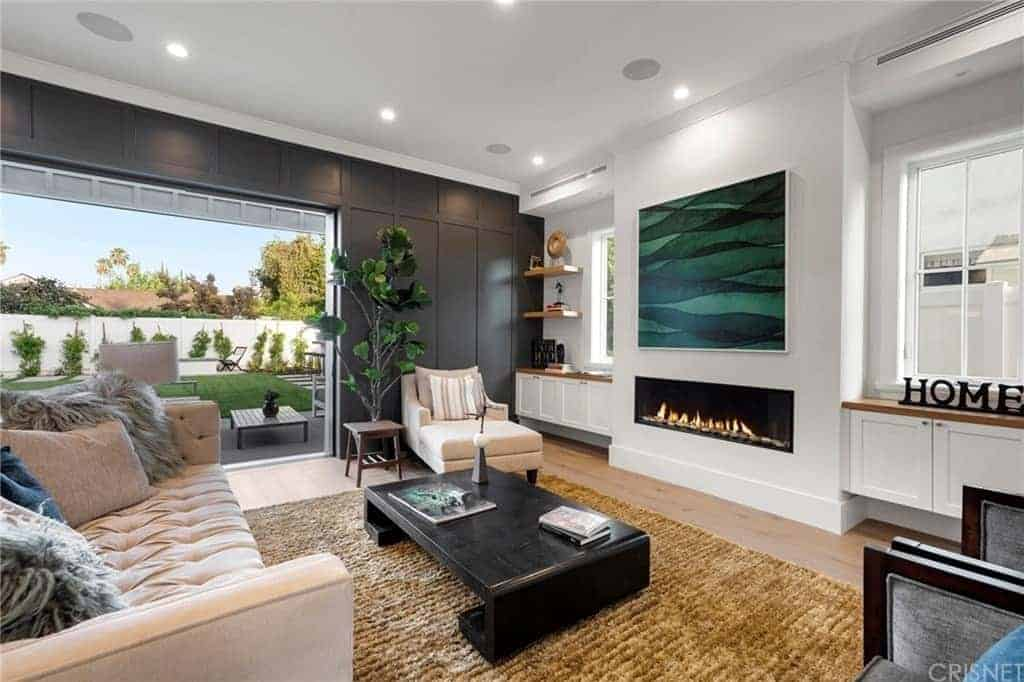 The modern fireplace that is built into the white wall is adorned with a large green painting mounted above it. This looks over a unique black wooden coffee table that complements the light pink cushioned sofa and the brown rustic area rug.