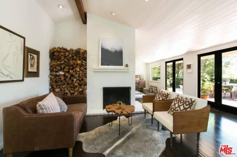 This Farmhouse-style living room has a dark hardwood flooring that is contrasted by the wall of the fireplace that also houses the fire wood on the side. This is paired with a brown leather sofa and couple of wooden armchairs with white cushions.