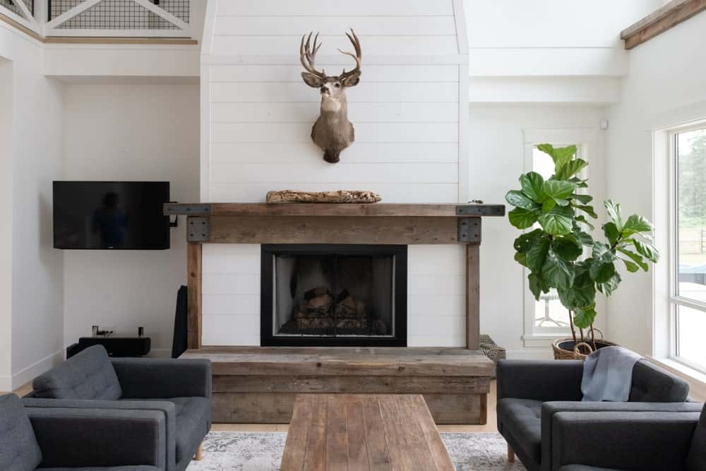 The centerpiece of this Farmhouse-style living room is the stuffed deer head mounted on the white wall above the fireplace that has a rustic wooden mantle that matches with the wooden coffee table flanked by dark gray cushioned armchairs.
