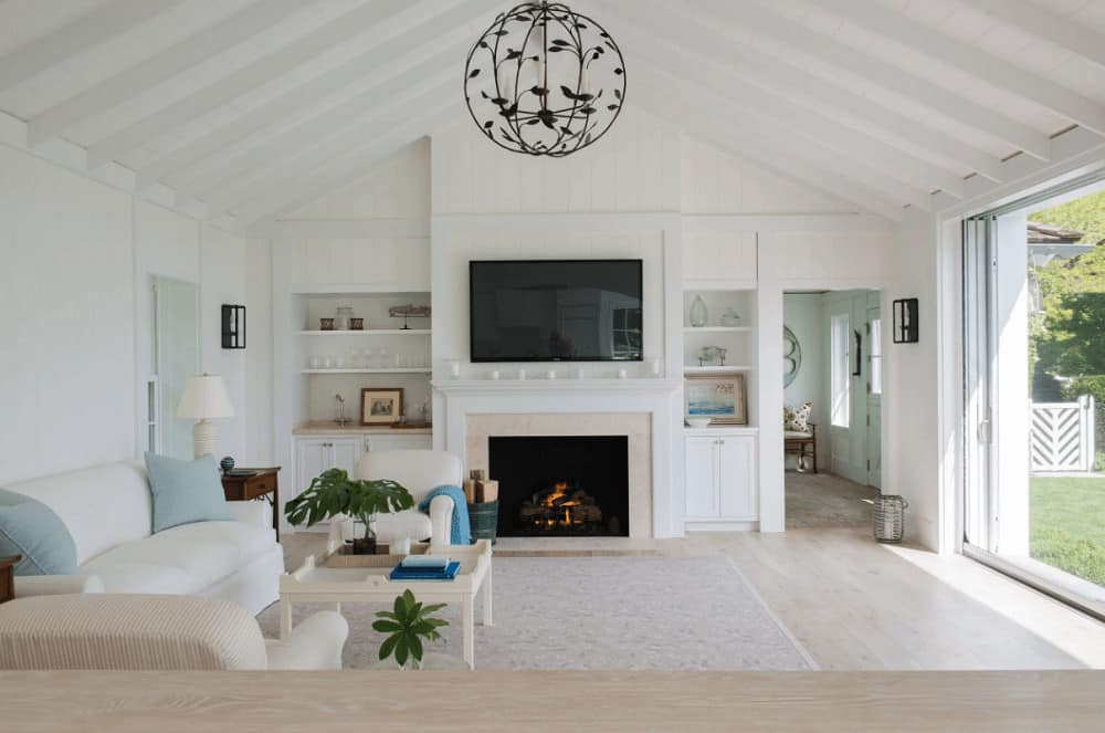 Cottage style living room showcases a fireplace with a flat-screen TV on top along with a gorgeous round chandelier that hung from the cathedral ceiling. It includes cozy seats and a wooden coffee table that blends in with the light hardwood flooring.