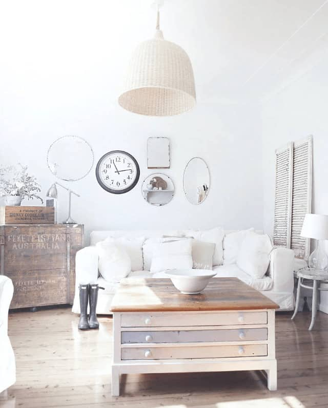 The bright living room features a wooden coffee table with storage lighted by a wicker dome pendant. It is decorated with a wall clock and various shaped mirrors mounted above the white sofa.
