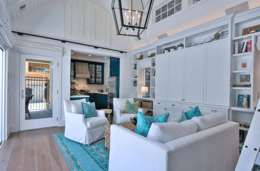 Charming blue rug and pillows add a nice accent in this white living room with skirted seats and a wicker ottoman illuminated by a lantern pendant light. It includes built-in cabinets surrounded by open shelving.