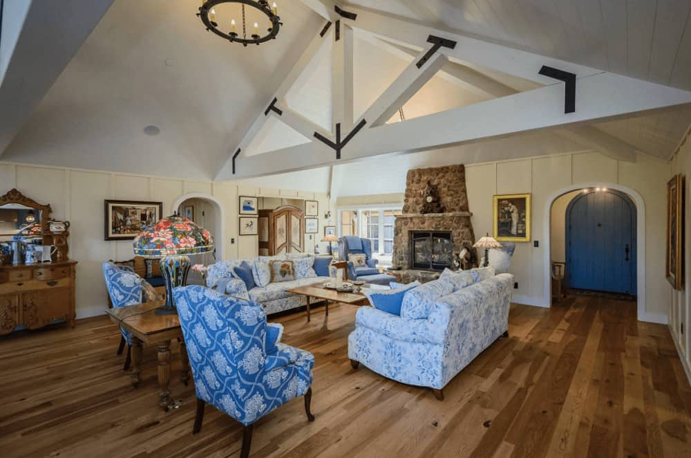 A colorful table lamp sits on the wooden side table flanked by blue patterned wingback chairs over the natural hardwood flooring. This room offers charming seats and a stone fireplace fixed on the beadboard wall.