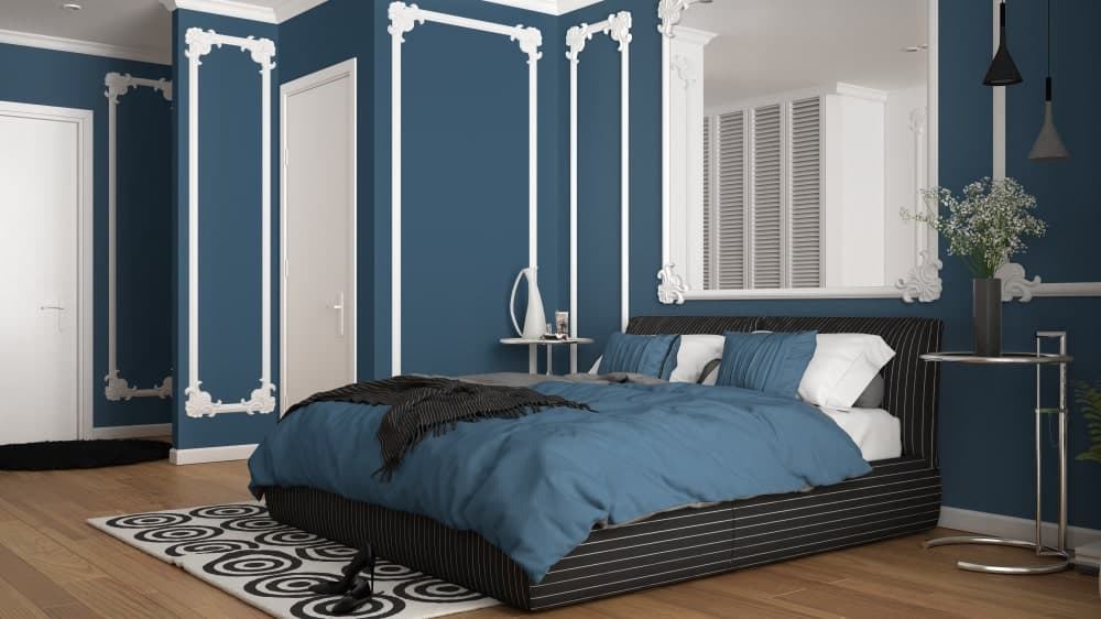 Classy primary bedroom designed with ornate wainscoting and a matching mirror that hung above the black striped bed flanked by round side tables.