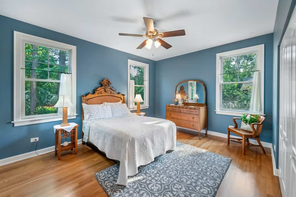 This bedroom is filled with a gray patterned rug and pieces of wood furniture that blend in with the hardwood flooring. It is illuminated by warm lamps from the ceiling fan along with natural light that flows in through the glazed windows.