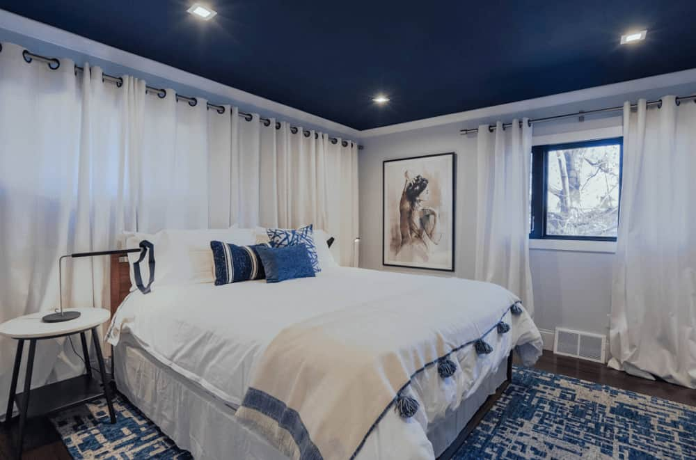 A blue printed rug lays on the dark hardwood flooring in this primary bedroom featuring a gorgeous painting and comfy bed illuminated by recessed ceiling lights.